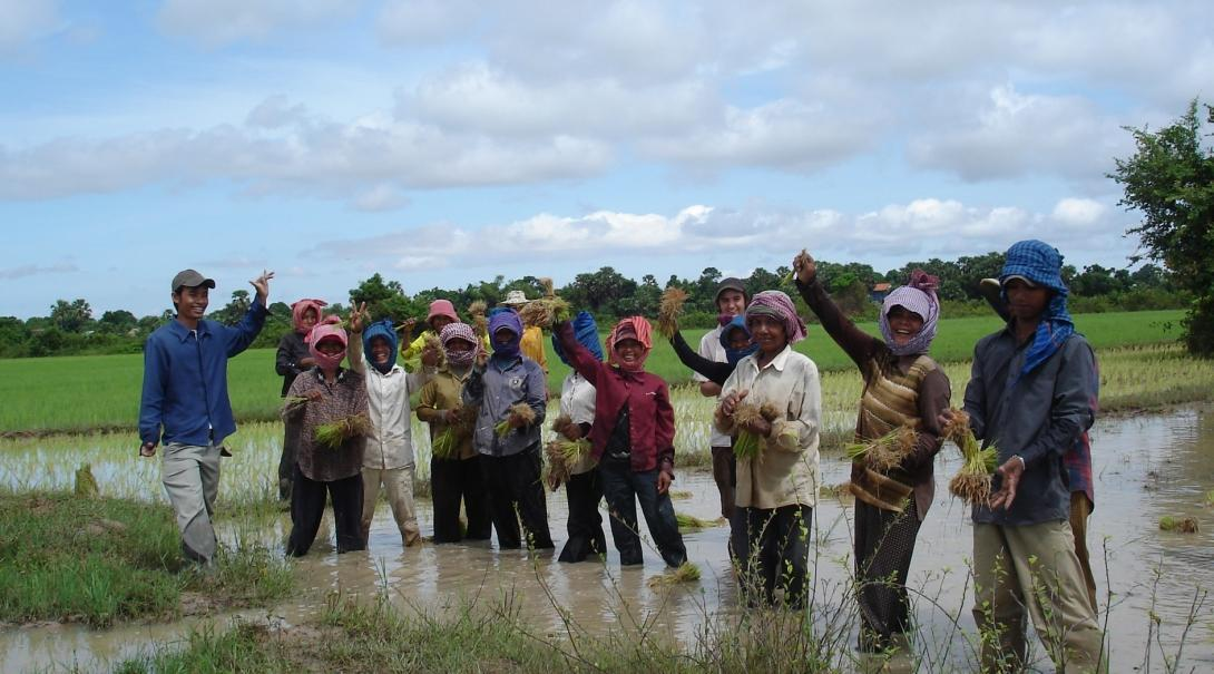 Local people are posing for a picture in a river during a Cultural immersion project in Cambodia.